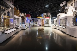 A wide-angle photo shows the Artifact Alley exhibition within the Canada Science and Technology Museum. A variety of artifacts are visible in cases on both sides of the image.