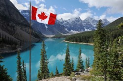 The Canadian flag, set against the backdrop of a clear, blue lake and mountains in Banff National Park, Alberta.