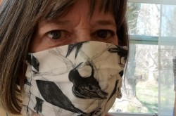 A close-up of a woman wearing a mask she made out of white fabric, with a crow pattern on it.