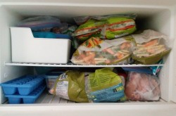 An open freezer filled with vegetables.