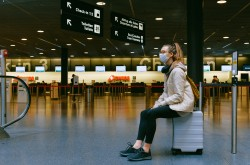 A young woman sits on her luggage in an empty airport terminal, gazing off into the distance to the left of screen. She is alone and wearing a blue medical mask, with headphones draped around her neck.