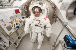 Astronaut Chris Hadfield, wearing a white spacesuit and helmet.
