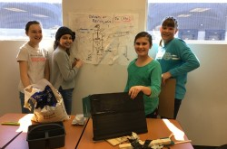 Four students, two in green shirts, two in grey shirts, stand on both sides of a poster with their invention drawn on it. Materials for building their invention are scattered in front of them.