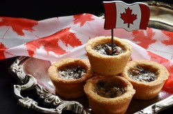 A stack of butter tarts sit on a silver platter; a small Canadian flag is inserted into the top butter tart.