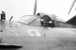 A black-and-white image shows a young male pilot in uniform, smiling as he looks out of the cockpit of an aircraft.