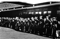 Image is a black-and-white photograph showing the first Canadian contingent of troops standing at attention before a train car.