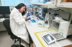 A young woman wearing a white lab coat and blue rubber gloves sits in a laboratory, working with a variety of tools in front of her.
