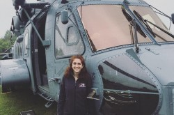 A young woman smiles as she stands next to a large helicopter, which is sitting on the grass.