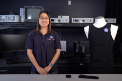 A young woman wearing a navy blue shirt smiles as she stands next to a mannequin dressed in a black tank top. A computer and a variety of equipment is visible on shelves in the background.