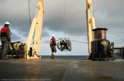 A crane on the back of a ship lowers an deep sea exploration robot while two workers observe