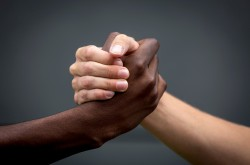 Two hands clasped together, one Black and one white, against a dark grey background.