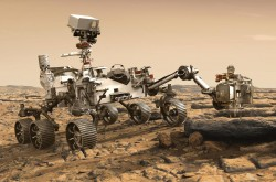 A six-wheeled rover is stationary on a light-coloured landscape. At the centre of the rover, a camera is mounted on top of a mast. A robotic arm is outstretched in front, and an instrument head at the end of the arm rests just above a rock.