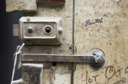 A close-up view of the latch of an old, wooden, graffiti-marked door.