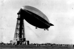 A black-and-white photograph showing a crowd gathered on the ground below the R-100, a massive blimp-like airship, tied to the top of a tall tower that looks like a lighthouse.