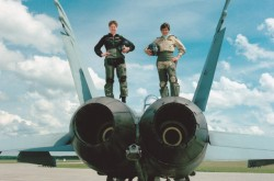 Two servicewomen in flight suits pose confidently atop a fighter jet at an airstrip on a clear blue day.